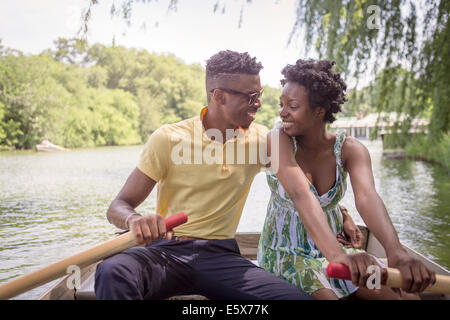 Young couple rowing on lake in Central Park, New York City, USA - Stock Photo