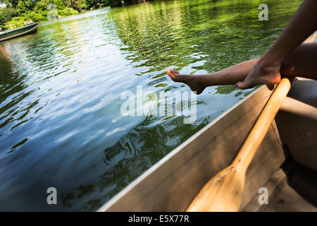 Cropped image of young woman's legs in rowing boat on lake in Central Park, New York City, USA - Stock Photo