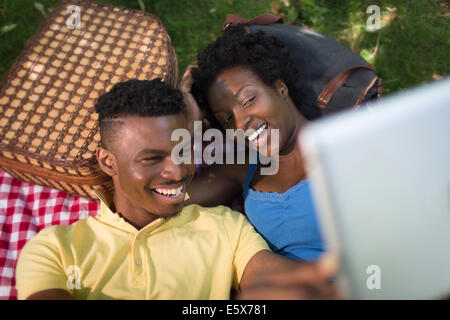Young couple in lying in park taking a selfie on digital tablet - Stock Photo