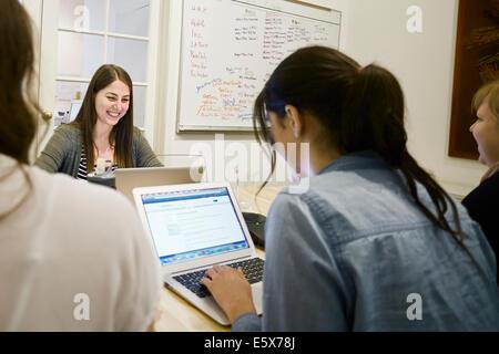 Women working on laptops in office - Stock Photo