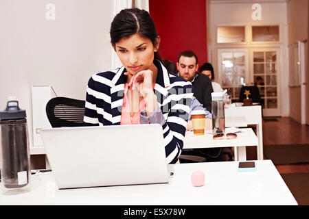 Row of people working on laptops in office - Stock Photo