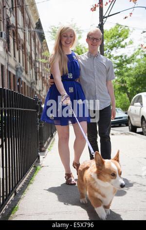 Young couple taking corgi dog for a walk along street - Stock Photo