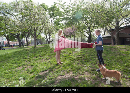 Young couple shaking picnic blanket in park