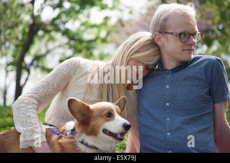 Young couple sitting in park with corgi dog - Stock Photo