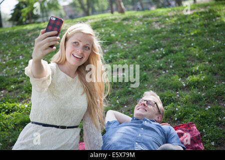 Young couple taking selfie with smartphone in park - Stock Photo