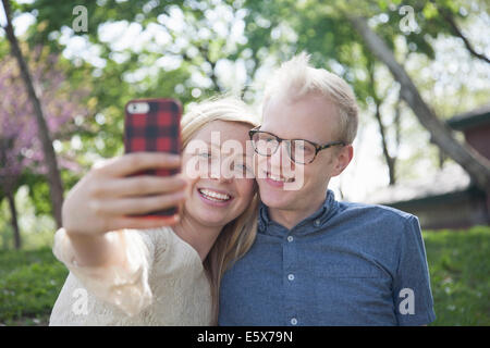 Young couple in park taking selfie with smartphone - Stock Photo