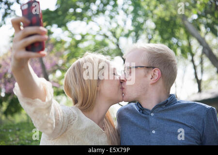 Young couple in park taking selfie whilst kissing - Stock Photo