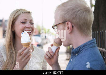 Young couple eating ice cream cones on street - Stock Photo