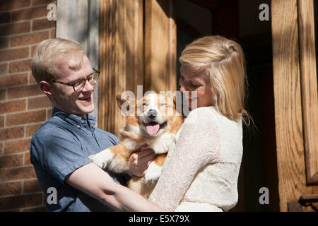 Happy young couple with corgi dog in arms outside front door - Stock Photo
