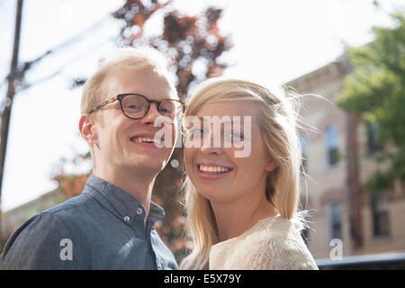 Portrait of happy young couple on street - Stock Photo