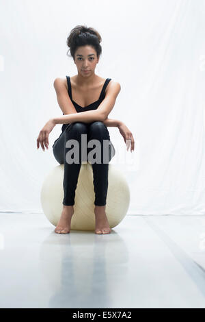 Studio portrait of confident young woman sitting on exercise ball - Stock Photo