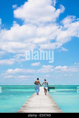 Young couple walking on pier, San Pedro, Belize - Stock Photo