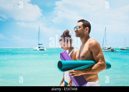 Young couple with yoga mats, San Pedro, Belize - Stock Photo