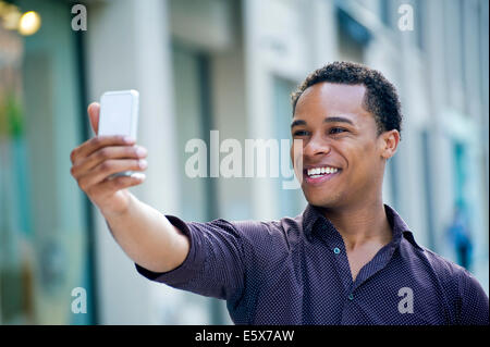 Young man taking smartphone selfie on city street - Stock Photo