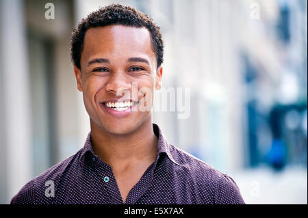 Portrait of young man chatting on city street - Stock Photo