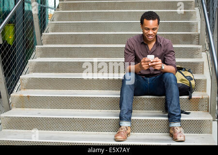Young man texting on smartphone on city stairway - Stock Photo