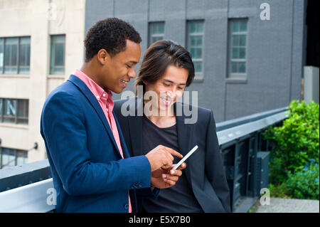 Two businessmen on city rooftop texting on smartphone - Stock Photo