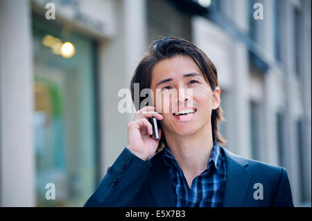 Mid adult businessman chatting on smartphone on city street - Stock Photo