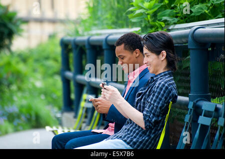 Two men on city park bench texting on smartphones - Stock Photo