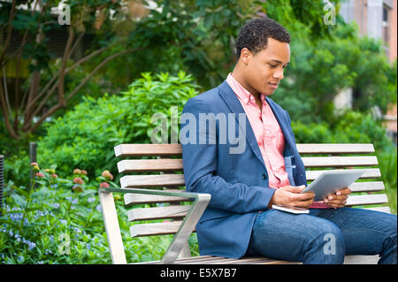 Young businessman sitting on park bench looking at digital tablet - Stock Photo