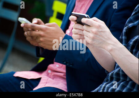 Cropped torso shot of young businessmen in city park texting on smartphones - Stock Photo