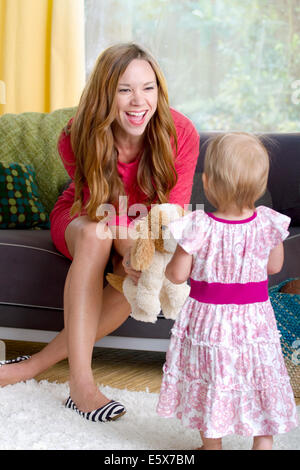 Mid adult mother playing with baby daughter and soft toy dog - Stock Photo