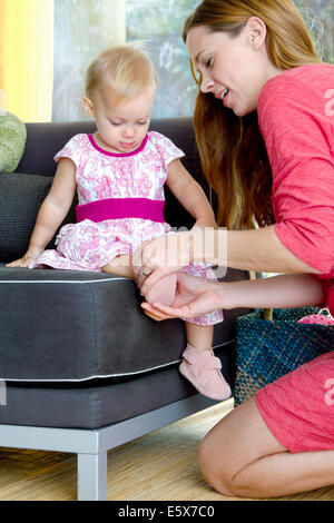 Mid adult mother putting on baby daughter's shoes - Stock Photo