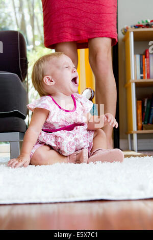 Legs of mid adult mother next to screaming baby daughter - Stock Photo