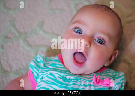 Overhead portrait of wide eyed baby girl - Stock Photo