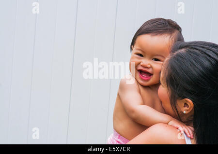 Portrait of mid adult mother and giggling baby boy - Stock Photo