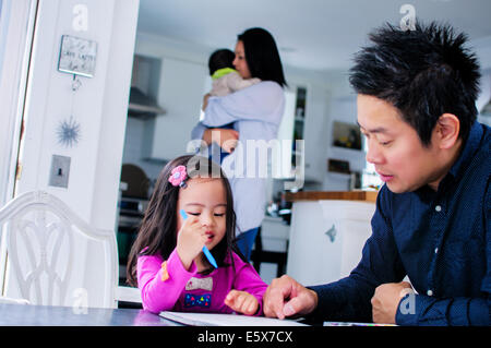 Mid adult father teaching toddler daughter in kitchen - Stock Photo