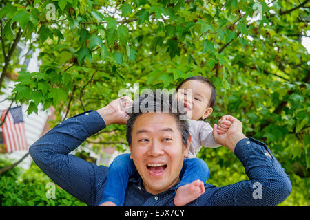 Mid adult father shoulder carrying baby son in garden - Stock Photo