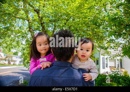 Portrait of mid adult father with baby boy and girl toddler over shoulder - Stock Photo