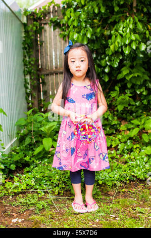 Portrait of serious young girl in garden with toy - Stock Photo