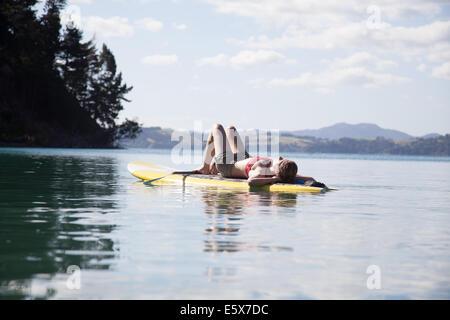 Mid adult woman sunbathing on paddleboard at sea - Stock Photo
