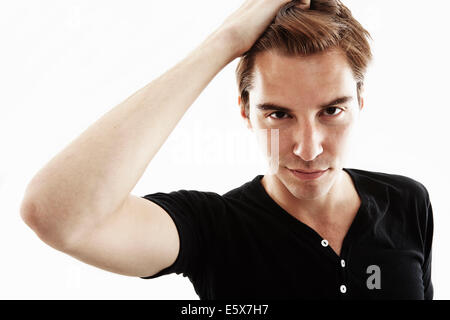 Studio portrait of young man with hand in hair - Stock Photo