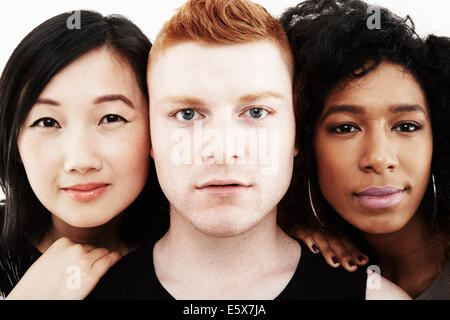 Close up studio portrait of one male and two female friends - Stock Photo