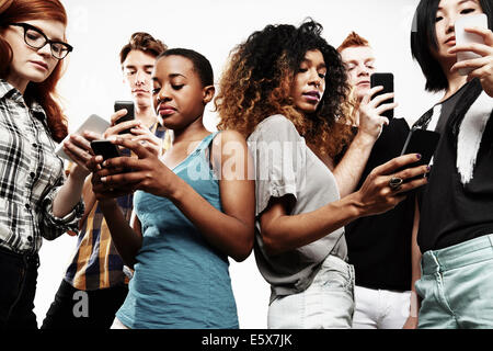 Low angle studio shot of six young adults texting on smartphone - Stock Photo