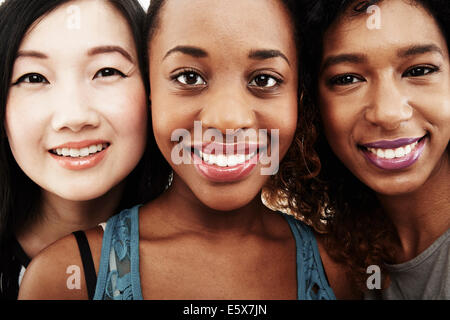 Close up studio portrait of three smiling young women - Stock Photo