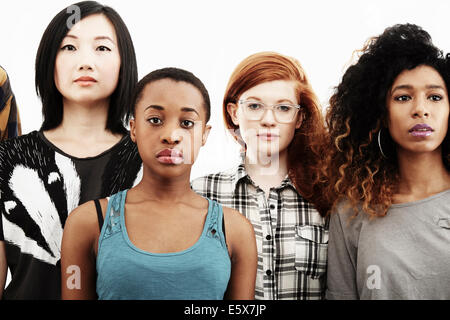 Formal studio portrait of four young women with blank expressions - Stock Photo