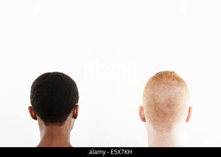 Rear view studio portrait of young couple's cropped hair - Stock Photo