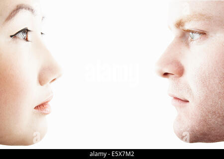 Close up studio portrait of young couple face to face in profile - Stock Photo