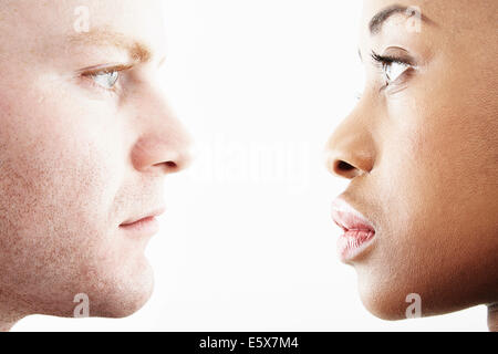 Cropped studio portrait of young couple face to face in profile - Stock Photo
