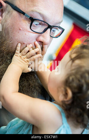 Close up of baby girl with hands over man's mouth - Stock Photo