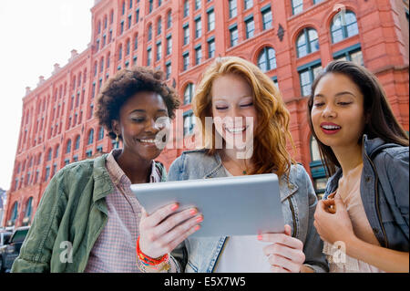 Three young women looking at digital tablet in street - Stock Photo