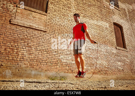 Young man exercising with skipping rope on wasteland