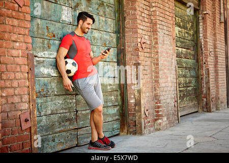 Young male soccer player texting on smartphone - Stock Photo