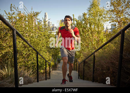 Young male runner running up park steps - Stock Photo