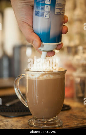 Close up of waiter squirting whipped cream onto cup of hot chocolate - Stock Photo
