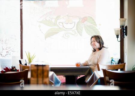 Mature woman having a herbal tea in cafe window seat - Stock Photo